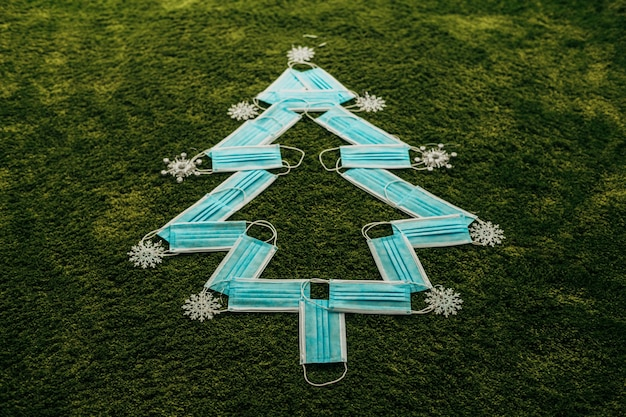 Christmas tree made of blue medical masks on a green background