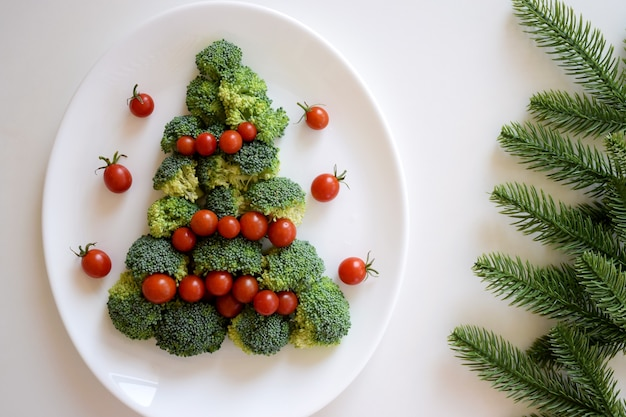 Christmas tree made of broccoli and cherry tomatoes on white plate with fir tree branches on white background. healthy organic food.
