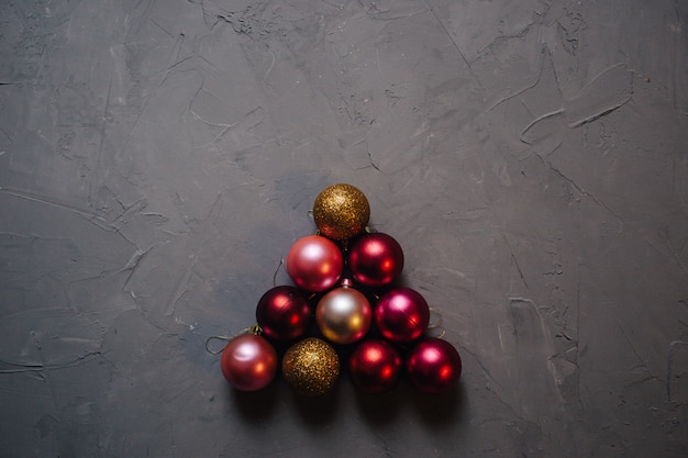 Christmas tree made by gold, red and pink christmas balls on the dark background, copy space