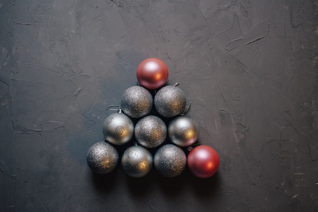 Christmas tree made by silver and pink christmas balls on the dark background, copy space