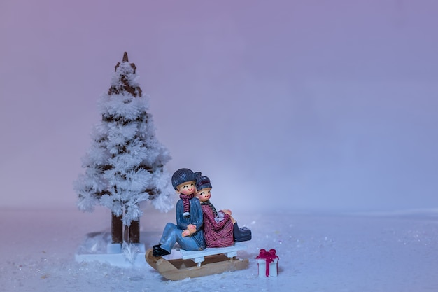 Christmas tree made of crystals, sleigh and sweet couple on snow.