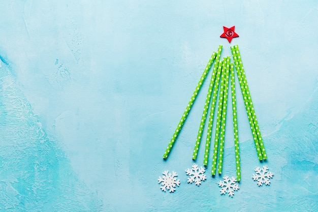 Christmas tree made of drinking colorful paper with white marshmallows and snowflakes toys on blue surface