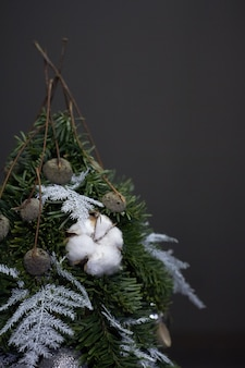 Christmas tree made of fir branches and decorated by natural materials and balls on dark