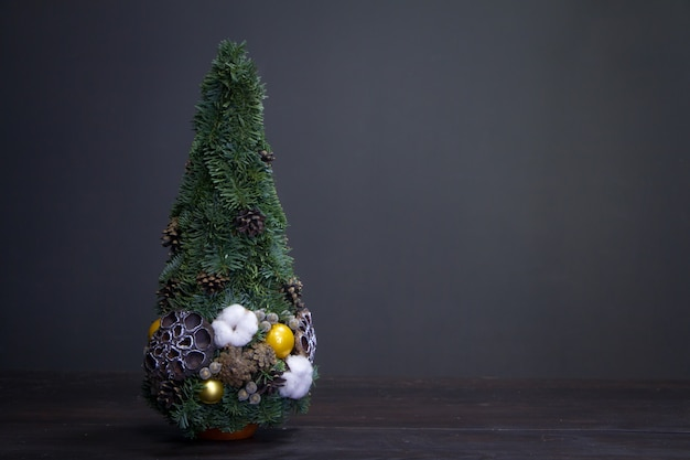 Christmas tree made of fir branches and decorated by natural materials and balls