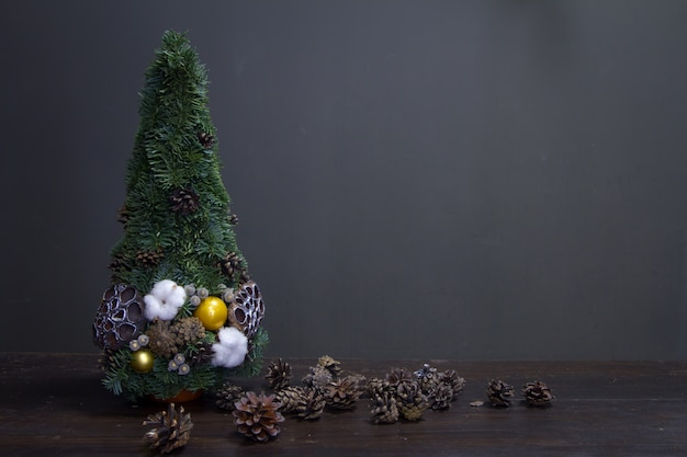 Christmas tree made of fir branches and decorated by natural materials and many cones