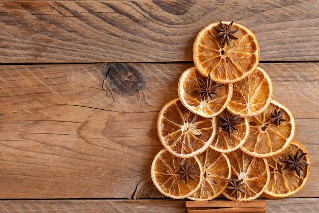 아니스 스타 씨앗, 계피 스틱, 오렌지 건조, 복사 공간 배경으로 만든 크리스마스 트리. 프리미엄 사진