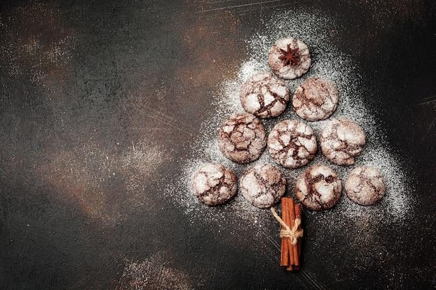 Елка из домового печенья с трещинами, корицей, колокольчиков и елочных игрушек на старой бетонной или каменной поверхности. новогодняя концепция