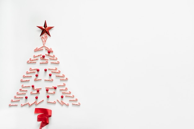 Christmas tree made from candy with red star and ribbon on white background