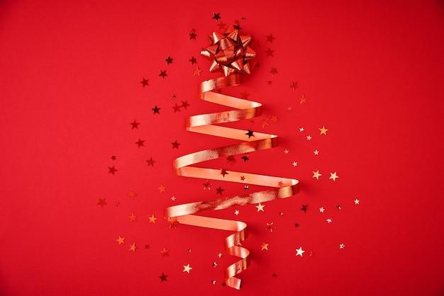 축제 리본 및 빨간색 배경에 색종이에서 만든 크리스마스 트리. 크리스마스 장식