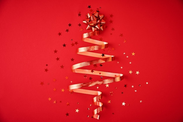 Christmas tree made from festive ribbon and confetti on red background. christmas decoration