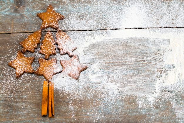 Christmas tree made from gingerbread cookies  on wooden background with copy space for text. holiday, celebration and cooking concept. new year and christmas postcard.