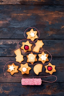Christmas tree made from homemade gingerbread cookies on old rustic wooden table. top view.