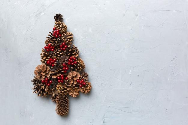 色付きの背景に自然な円錐形で作られたクリスマスツリー、上からの眺め。コピースペースのある新年のミニマルコンセプト。