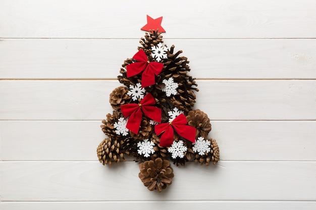 Рождественская елка из натуральных шишек на цветном фоне, вид сверху. новогодняя минимальная концепция с копией пространства