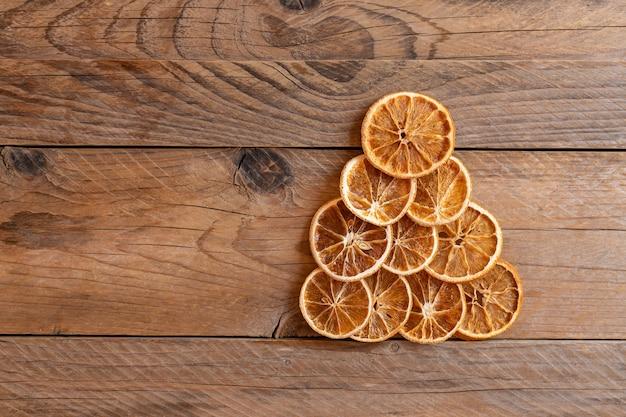 복사 공간 배경으로 오렌지 건조로 만든 크리스마스 트리. 겨울 휴가를 위한 최소한의 개념