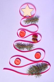 Новогодняя елка из ленты, украшенная свечами еловыми ветками и звездой на верхушке елки