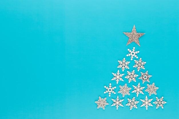 Рождественская елка из хлопьев белого снега на красном фоне. новогодняя и рождественская открытка.