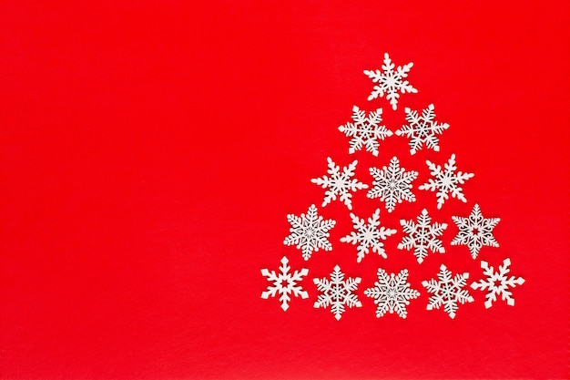 Christmas tree made from white snow flake decorations on red  background with empty copy space for text. new year and christmas postcard.