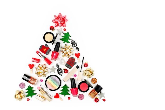 흰색 바탕에 겨울 장식과 화장품으로 만든 크리스마스 트리. 휴일 및 축하 창의적인 개념입니다. 평평한 평지, 평면도