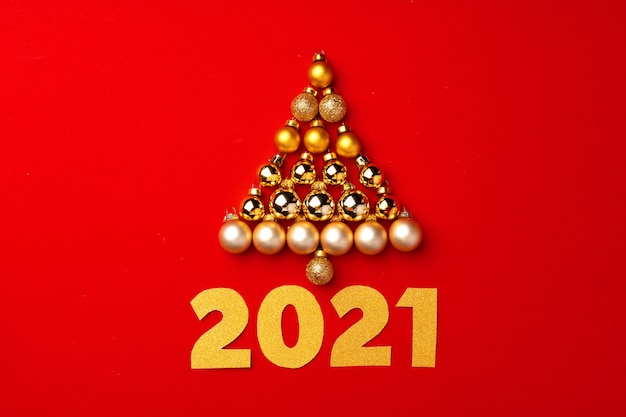 Christmas tree made of gold baubles on red background top view