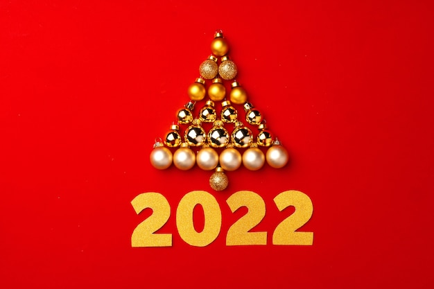 Christmas tree made of gold baubles on red background