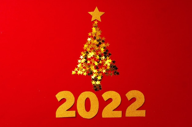 Christmas tree made of gold confetti on red background top view