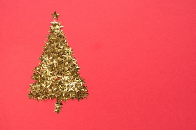 Christmas tree made of golden stars glitter confetti on red background. xmas holiday .