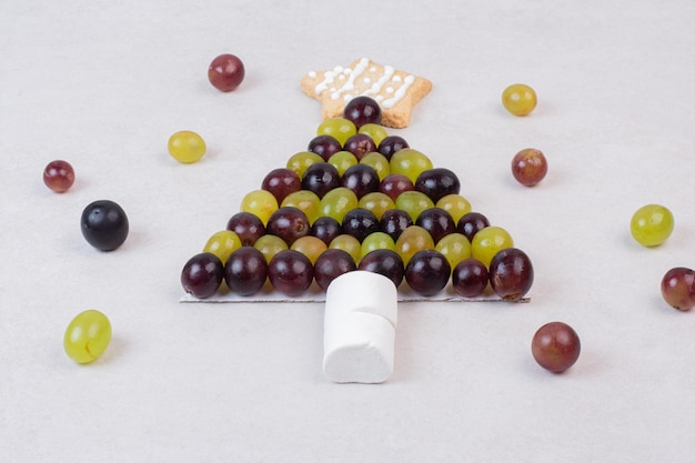 Albero di natale fatto di uva, biscotti e marshmallow.