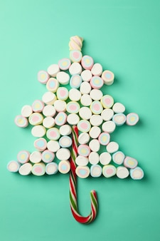Christmas tree made of marshmallows on mint surface