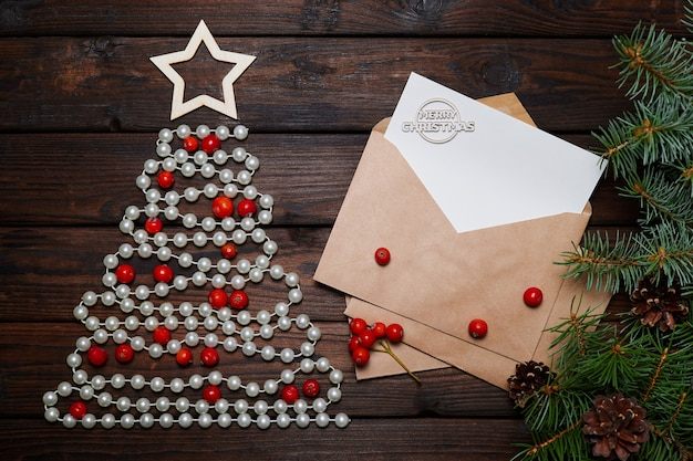 メリークリスマスの碑文と封筒にビーズと手紙で作られたクリスマスツリー