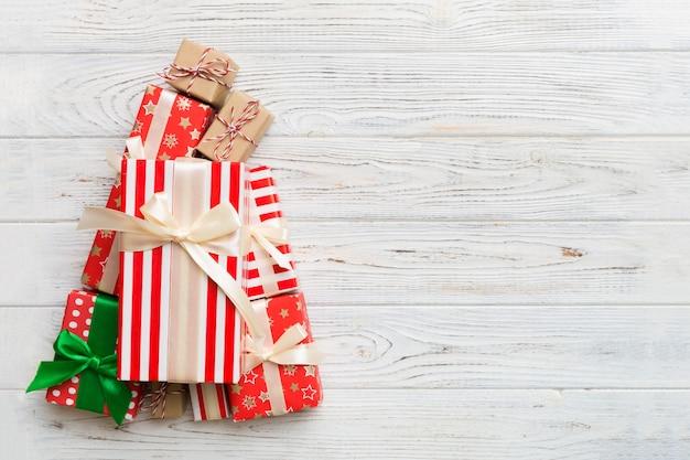 色付きの背景に美しく包まれたプレゼントで作られたクリスマスツリー、上からの眺め。コピースペースと新年のギフトボックスの最小限の概念