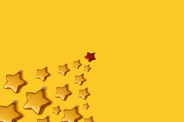 파란색 별 모양의 값싼 물건 장식으로 만든 크리스마스 트리. 노란색 배경에 최소한의 새 해 개념입니다. 크리스마스 카드 또는 벽지 패턴입니다. 크리스마스 정신.