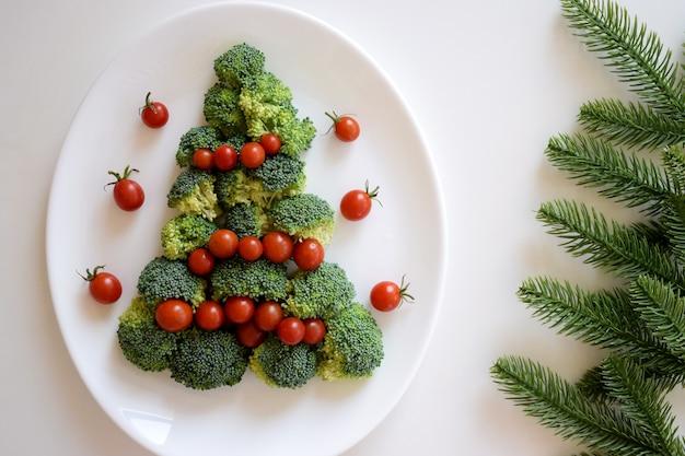 白いプレートにブロッコリーとチェリートマトで作られたクリスマスツリー、白い背景にモミの木の枝。健康的な有機食品。