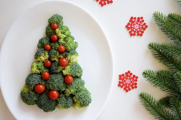 ブロッコリーと小さなトマトで作られたクリスマスツリー。白いプレートに赤い雪片と白い背景にモミの木の枝があります。