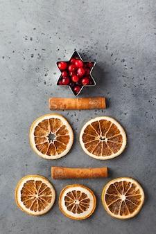 회색 콘크리트 표면에 설탕에 절인 오렌지, 계피 스틱, 크랜베리로 만든 크리스마스 트리