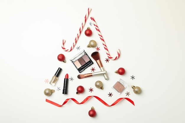 白い背景の上の化粧品とつまらないもので作られたクリスマスツリー