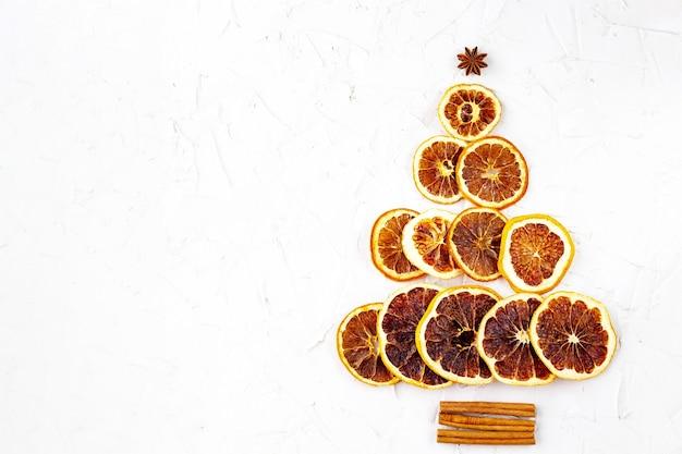 乾燥した柑橘類とシナモン、白い背景の上のアニスで作られたクリスマスツリー。オレンジ、レモン、モミの木の形をしたグレープフルーツ