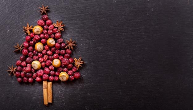 Рождественская елка из сушеной клюквы, орехов, палочек корицы и звездочки аниса на темном фоне, вид сверху с копией пространства