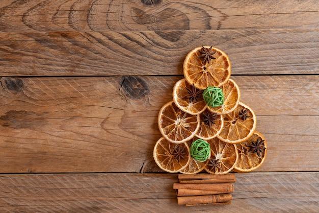 나무 배경에 말린 오렌지, 계피, 스타 아니스로 만든 크리스마스 트리. 텍스트를 위한 공간을 복사합니다.