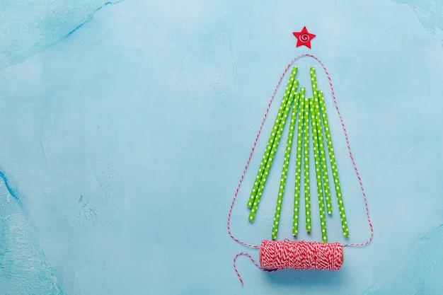 青い背景にカラフルな紙を飲むことで作られたクリスマスツリー。新年のコンセプト。