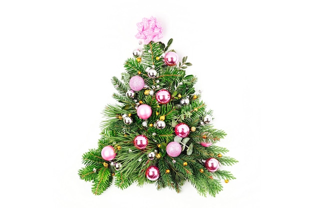 白い背景の上のクリスマスの装飾とモミと松の枝で作られたクリスマスツリー。休日のコンセプト。フラットレイ、上面図