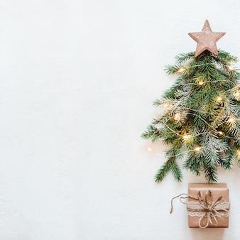 木の星と紙のレースの贈り物とモミの枝で作られたクリスマスツリー。ゼロウェイストクリスマスのコンセプト。