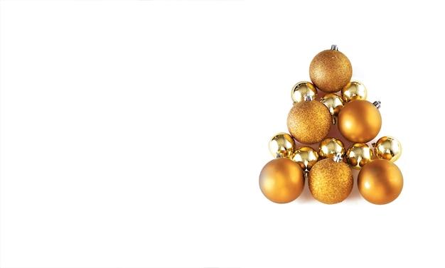 白い孤立した背景に金色の安物の宝石の装飾で作られたクリスマスツリー