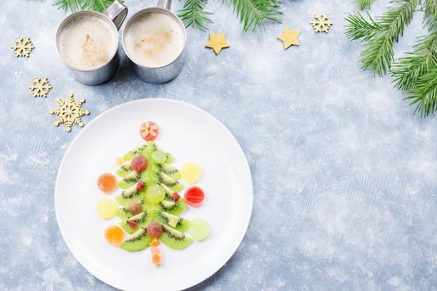 モミの枝と装飾が施されたプレートにキウイとフルーツゼリーで作られたクリスマスツリー。上面図、コピースペース