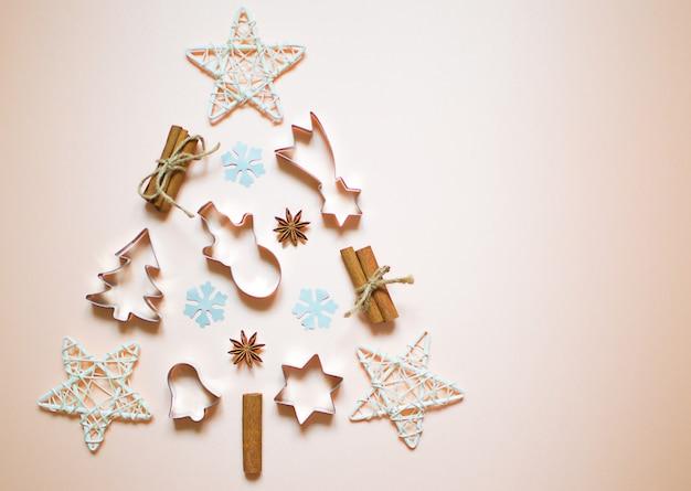 Елка из новогодних украшений. зимние вещи на светлом фоне. праздничная открытка. плоская планировка, минимальная