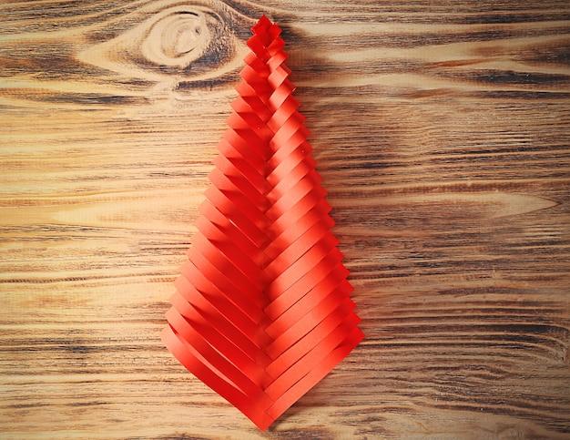 木製の背景に紙で作られたクリスマスツリー