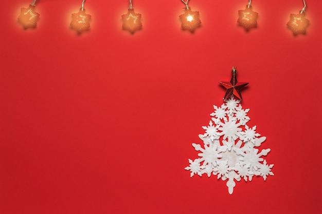 종이 눈송이와 빨간색 배경에 조명 된 갈 랜드로 만든 크리스마스 트리. 크리스마스와 연말 연시.