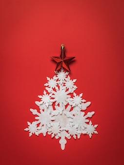 빨간 별을 가진 종이 눈송이의 크리스마스 트리에 의하여 이루어져있다. 크리스마스와 연말 연시.