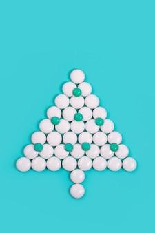 Новогодняя елка из таблеток. новый год в медицине, аптеке и аптеке. фармацевтика. покупка лекарств для здоровья во время рождественских праздников. креативный минимализм на зеленом фоне. скопируйте пространство.
