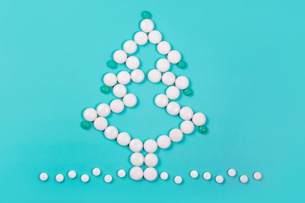 Новогодняя елка из таблеток. новый год в медицине, аптеке и аптеке. фармацевтика. покупка лекарств для здоровья во время рождественских праздников. креативный минимализм на зеленом фоне.
